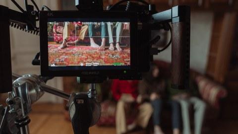 durch eine Filmkamera sind nackte Füße von Menschen zu sehen, die auf einem bunten Sofa sitzen.