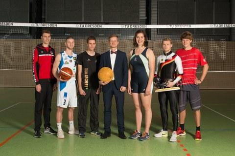 Foto mit den sechs Sportstipendiaten und dem Kanzer vor dem Volleyball-Netz in der Sporthalle