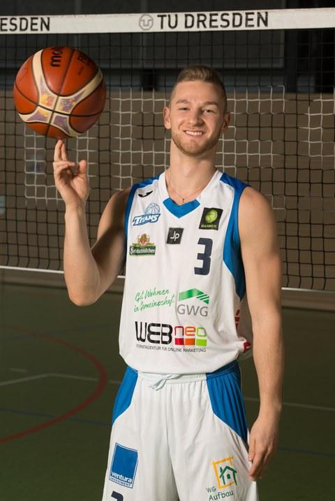 Foto von Bryan Nießen, Sportstipendiat der TUD 2019 in Sportkleidung und mit Basketball
