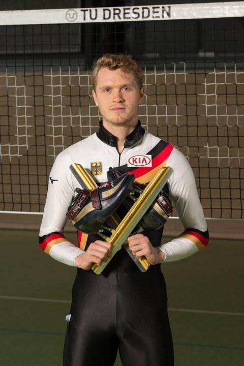 Foto mit Leon Kaufmann-Ludwig, Sportstipendiat 2019. Er steht im Deutschland-Sportdress mit vor der Brust gehaltenen Schlittschuhen in der Turnhalle vor dem Volleyball-Netz.