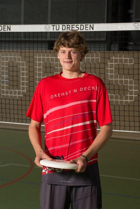 Foto mit Jakob Dieckmann, Sportstipendiat 2019. Er steht im Sportdress mit einem Frisbee in der Hand vor dem Volleyballnetz in der Turnhalle