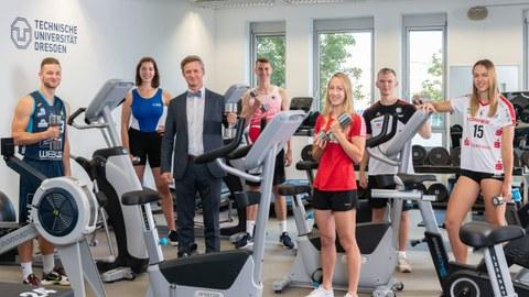 Gruppenbild 6 Sportstipendiat:innen mit Kanzler Handschuh im neu eingerichteten TUD Fitnessraum zwischen Fahrradtrainern, alle mit Hantel in der Hand