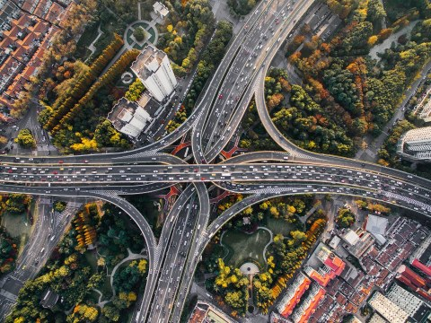 Das Foto zeigt eine Liftaufnahme einer sehr großen Kreuzung mit vielen Autos in einer großen Stadt von oben.