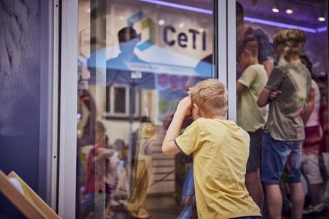 Das Foto zeiht ein Kind von hinten, was durch eine Scheibe in einen Raum schaut. Im Raum sind viele weitere Kinder zu sehen.