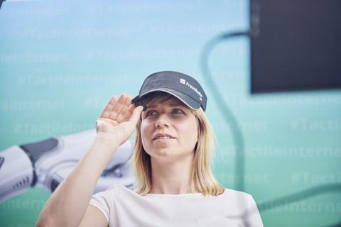 Eine Frau mit Mütze blickt in eine winzige Kamera.
