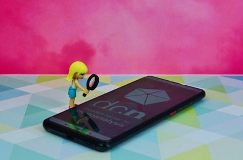 Das Bild zeigt ein weiblich Legofigur die mit einer Lupe auf ein Handy schaut.