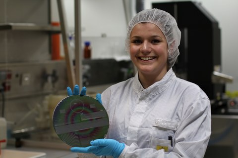 Das Bild zeigt eine Frau mit Haarhaube, die einen Waver in der Hand hält.