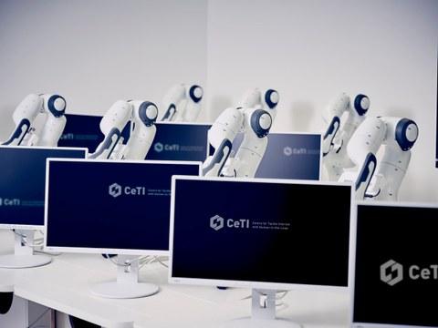 Das Bild zeigt Bildschirme und Roboterarme hintereinander angeordnet.