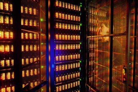 Das Foto zeigt einen Serverraum. Hinter eine Glasscheibe ist eine Frau zu erkennen.