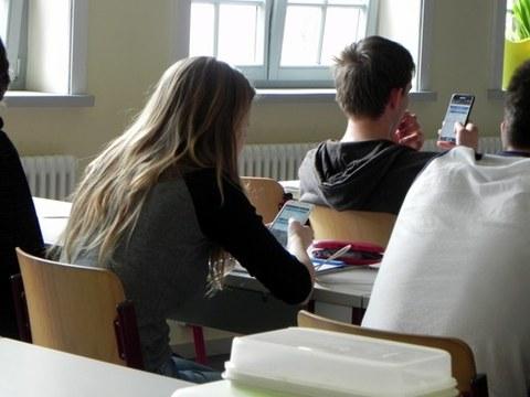 Das Foto zeigt Schülerinnen und Schüler in einer Unterrichtssituation, die ihr Smartphone benutzen. Die Schülerinnen und Schüler sind nur von hinten zu sehen.
