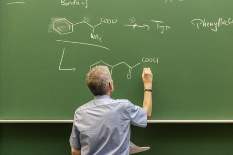 Das Foto zeigt einen Mann, der chemische Formeln auf eine Tafel schreibt.