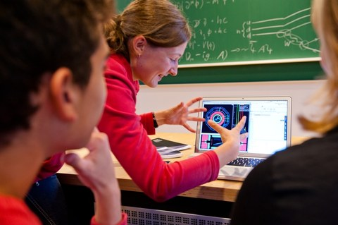 Photo of a woman using graphics to explain something on her laptop. Two people are watching her. In the background there is a blackboard with formulas and drawings.