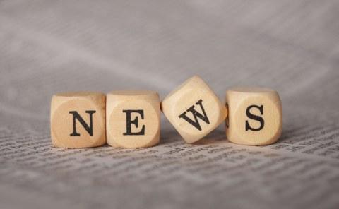 """Foto mit vier Holzwürfeln, die auf einem bedruckten Blatt Papier liegen. Auf jedem Würfel steht ein Buchstabe. Die Buchstaben ergeben das Wort """"News""""."""