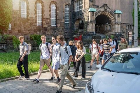 Foto einer Gruppe von jungen Leuten, die hintereinander auf einem Bürgersteig laufen.