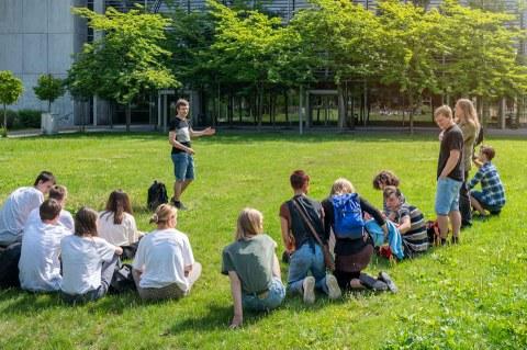 Foto. Eine Gruppe von Personen sitzt auf einer Wiese. Im Hintergrund ist ein Gebäude zu sehen, vor dem Bäume stehen.