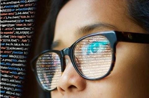 Foto. Zu sehen ist der obere Teil eines Gesichts. In der Brille spiegelt sich die Oberfläche eines Bildschirms mit Codes.