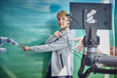 """Foto einer jungen Frau, die den Blick auf einen Bildschirm im Vordergrund gerichtet hat. Ihr Körper ist nach rechts gedreht. Ihr linker Arm zeigt auf eine Roboterhand. Im Hintergrund ist eine Leinwand zu sehen auf der mehrmals """"#TactileInternet"""" steht."""