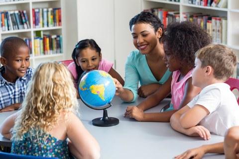 Auf dem Foto sitzen Kinder an einem Tisch. In der Mitte des Tisches steht ein Globus. Eine Frau zeigt auf eine bestimmte Stelle auf dem Globus.