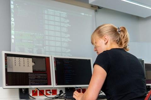 Foto: Vor einer Leinwand mit Datencodes schreibt eine Frau auf einer Tastatur vor zwei Monitoren.