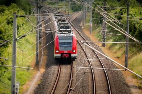 Foto eines roten Zuges auf Schienen mit Oberleitungen.