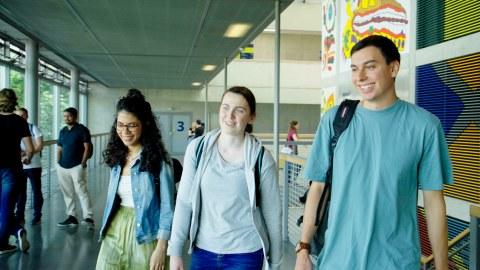 drei Studierende laufen durch das HSZ und unterhalten sich