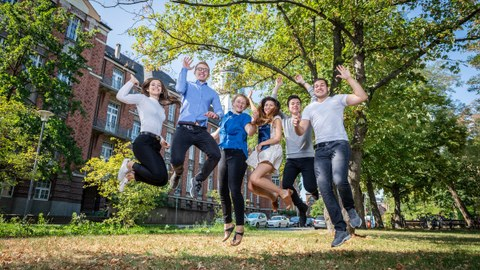Six students jump into the air in front of the Beyer Building of the TU Dresden