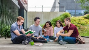 Photo: Five happy students sitting on a wooden terrace of the Andreas Pfitzmann Building