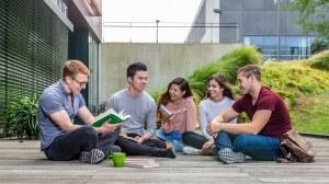 Eine Gruppe Studierender sitzt im Außengelände auf eine Terrasse des Informatik-Gebäudes