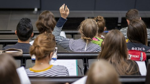 Photo of students in a lecture in a lecture hall from behind. One of them reports in