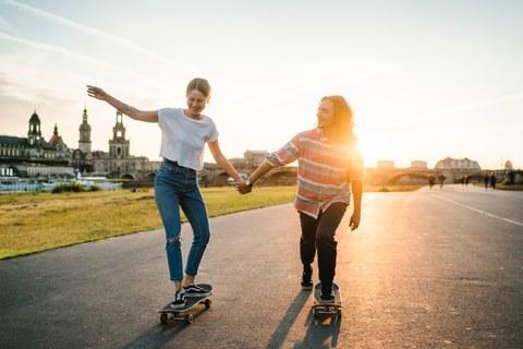 Eine junge Frau und ein junger Mann fahren mit dem Skateboard am Elbufer und halten sich an den Händen. Im Hintergrund befindet sich die Skyline von Dresden.