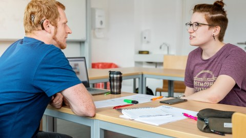 Das Foto zeigt zwei Studierende in einem Seminarraum. Sie sitzen sich gegenüber und sprechen miteinander. Zwischen ihnen liegen Zettel und Stifte. Einer der beiden Studierenden trägt ein Hörgerät.