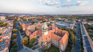 Das Foto zeigt eine Luftaufnahme des Georg-Schumann-Baus der TU Dresden. Das Gebäude wirkt wie eine Art Burg. Besonders auffällig sind der große Wehrturm und die spitzen Dächer.