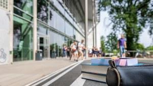 Das Foto zeigt das Hörsaalzentrum der TU Dresden. Im Fokus stehen zwei Bücher und eine Federmappe. Sie liegen auf der Treppe vor dem Hörsaalzentrum