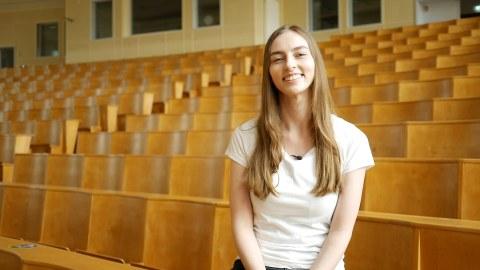 Studentin Rebecca sitzt im leeren Hörsaal und schaut in die Kamera.