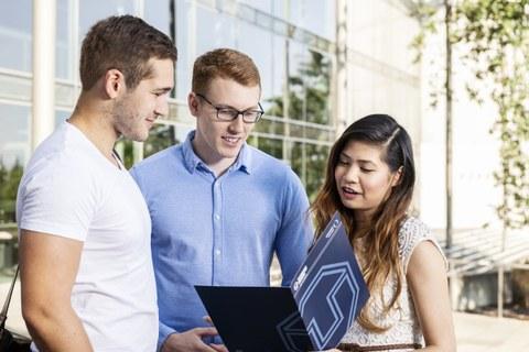 Drei Studierende stehen vorm dem Hörsaalzentrum. Die Studentin hält eine TU Dresden Mappe in der Hand und zeigt diese den beiden Studenten neben ihr.