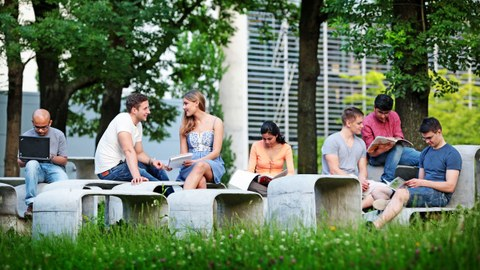 The photo shows several students outside in the green. They sit on a curved concrete formation of tables and benches and study.