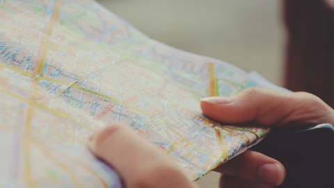 In der Hand wird ein Stadtplan gehalten für die Anreise