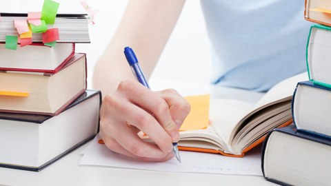 Zwei Stapel Bücher liegen auf dem Tisch. In der Mitte ist eine Hand mit einem Stift zusehen mit einem Blatt Papier.