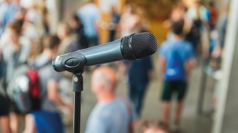 im Vordergrund ein Mikrofone und mit Menschen im Hintergrund