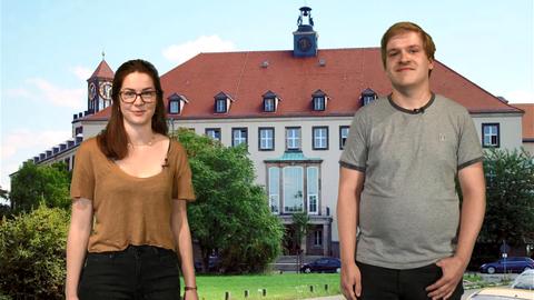 Zwei Studierende stehen auf dem Uni-Campus.