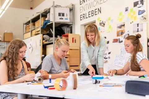 Drei junge Frauen sitzen am Tisch und eine Frau steht am Tisch. Auf dem Tisch liegen viel Papier, Schere, Leim und Stifte. Die Frauen basteln aus dem Papier Modelle.