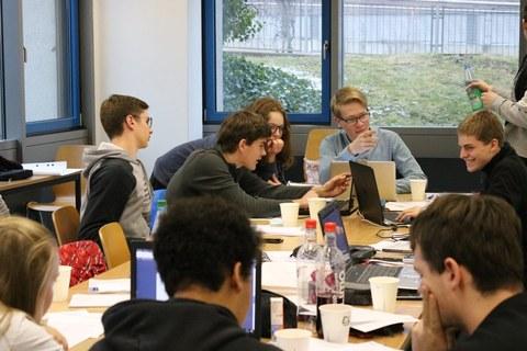 Schülerinnen und Schüler diskutieren intensiv in Kleingruppen.