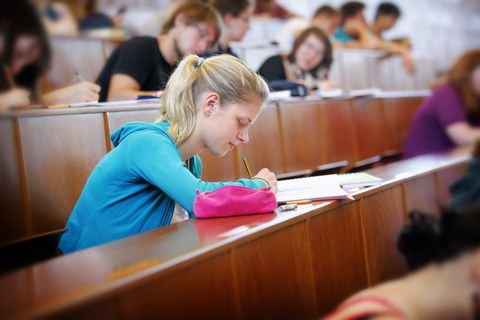 The photo shows a lecture hall full of students. The focus is on a female student. She is taking notes with a pencil in her documents.