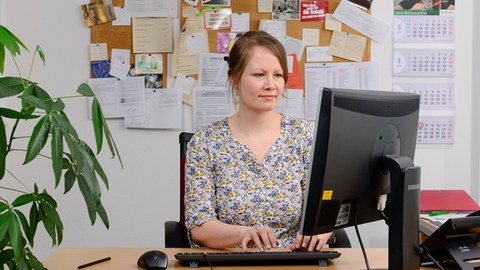The image shows a photo of a student counsellor. She is sitting at her workplace in front of her PC and typing on the keyboard.