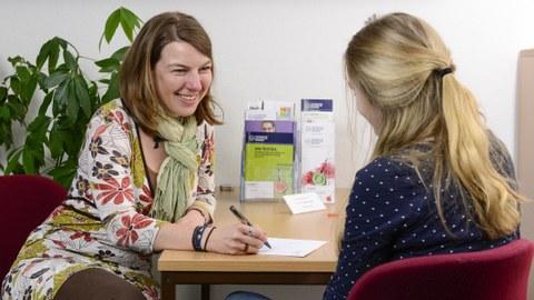 Es ist ein Foto zu sehen, auf dem zwei Personen abgebildet sind. Sie sitzen sich gegenüber an einem Tisch. Die Person links im Bild ist eine Studienberaterin, welche sich Notizen macht. Die zweite Person ist nur von hinten zu erkennen.