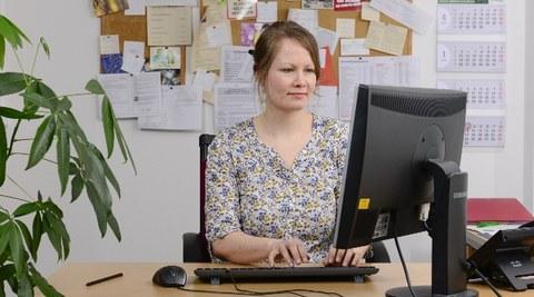Das Bild zeigt ein Foto von einer Studienberaterin. Sie sitzt an ihrem Arbeitsplatz vor ihrem PC und tippt auf der Tastatur.