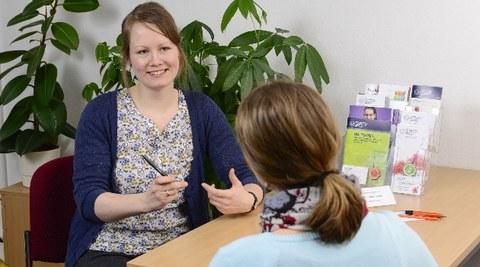 Es ist ein Foto zu sehen, auf dem zwei Frauen abgebildet sind. Sie sitzen an einem Tisch und sprechen miteinander. Eine Person sitzt mit dem Rücken zur Kamera. Die andere Person ist gut zu erkennen und gestikuliert mit ihren Händen.
