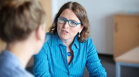 Das Foto zeigt ein Gespräch zweier Personen während einer Studienberatung. Die Studienberaterin schaut in Richtung Kamera, die andere Person ist von hinten zu sehen.
