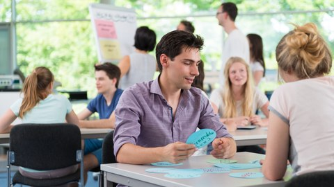Es ist eine Momentaufnahme aus einem Workshop in einem hellen Seminarraum zu sehen. Einige Studierende sitzen in Zweiergruppen an jeweils einem Tisch. Andere stehen im Hintergrund mit einer Studienberaterin vor einem Flipchart.