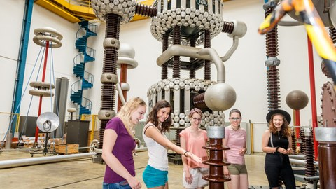 The picture shows a photo of five girls in the high-voltage hall of the TU Dresden. The girls are looking at the model of an electromagnet.
